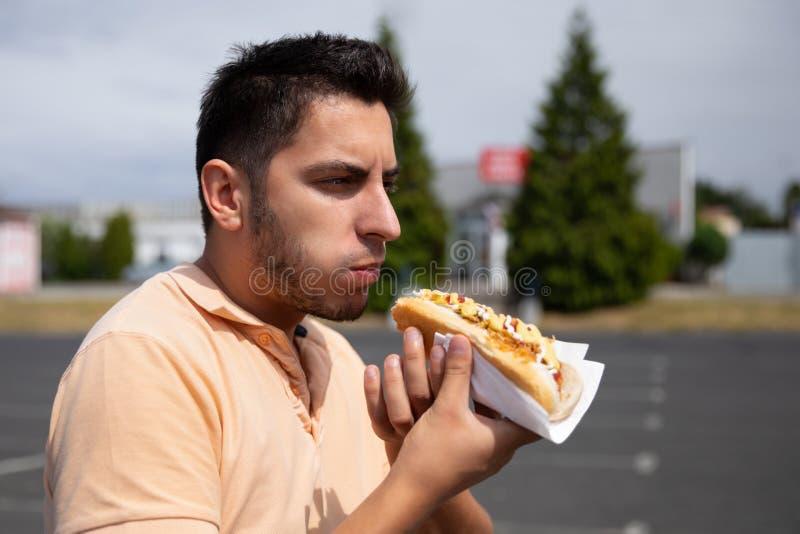 Przystojny brunetka mężczyzny łasowania hot dog w parking zdjęcie royalty free