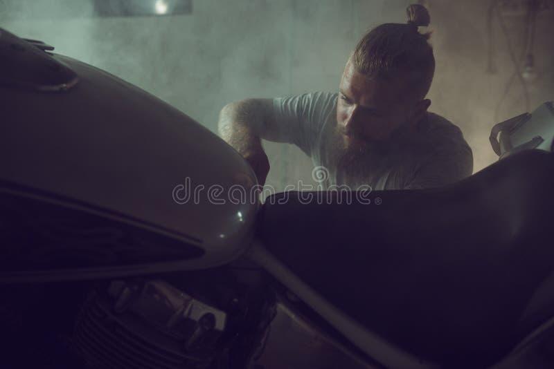 Przystojny brutalny mężczyzna naprawia motocykl w jego garażu z brodą obraz royalty free