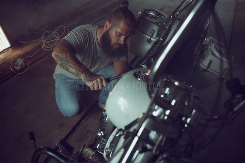 Przystojny brutalny mężczyzna naprawia motocykl w jego garażu z brodą obrazy stock