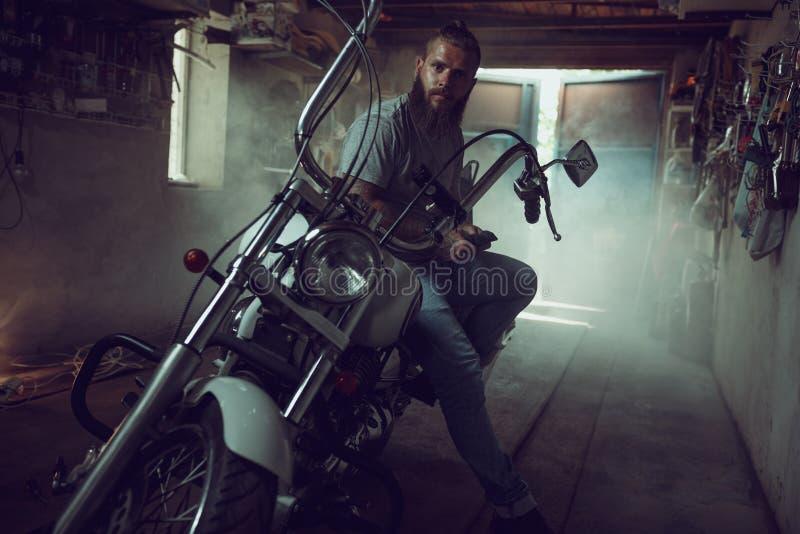 Przystojny brutalny mężczyzna z brody obsiadaniem na motocyklu w jego garażu, obcieranie jego ręki i patrzeć strona zdjęcia stock