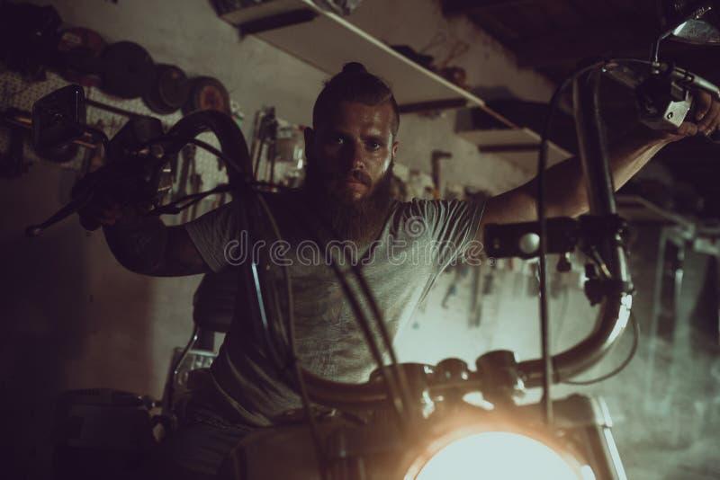 Przystojny brutalny mężczyzna z brody obsiadaniem na motocyklu w jego garażu, obcieranie jego ręki i patrzeć strona fotografia royalty free