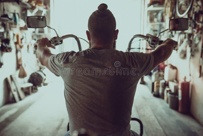 Przystojny brutalny mężczyzna z brody obsiadaniem na motocyklu w jego garażu, widok od plecy zdjęcie royalty free