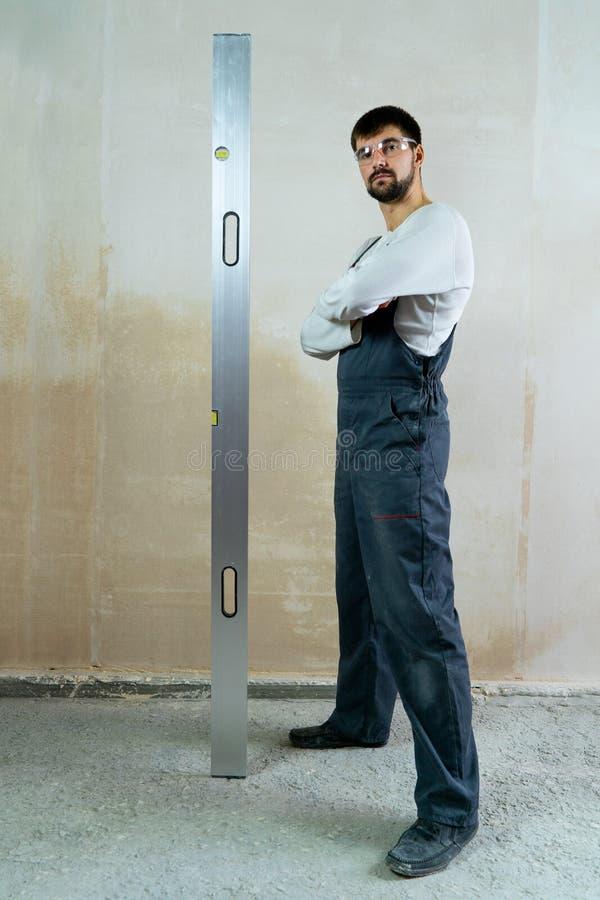 Przystojny budowniczy z rękami składać stoi blisko pustej ściany z budowy władcą zdjęcia royalty free