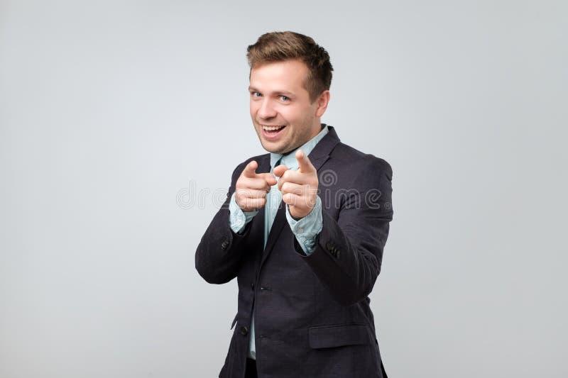 Przystojny caucasian facet wyraża pozytywne emocje w kostiumu podczas gdy wskazujący przy kamerą z wskaźnika pistoletem podpisuje zdjęcia stock