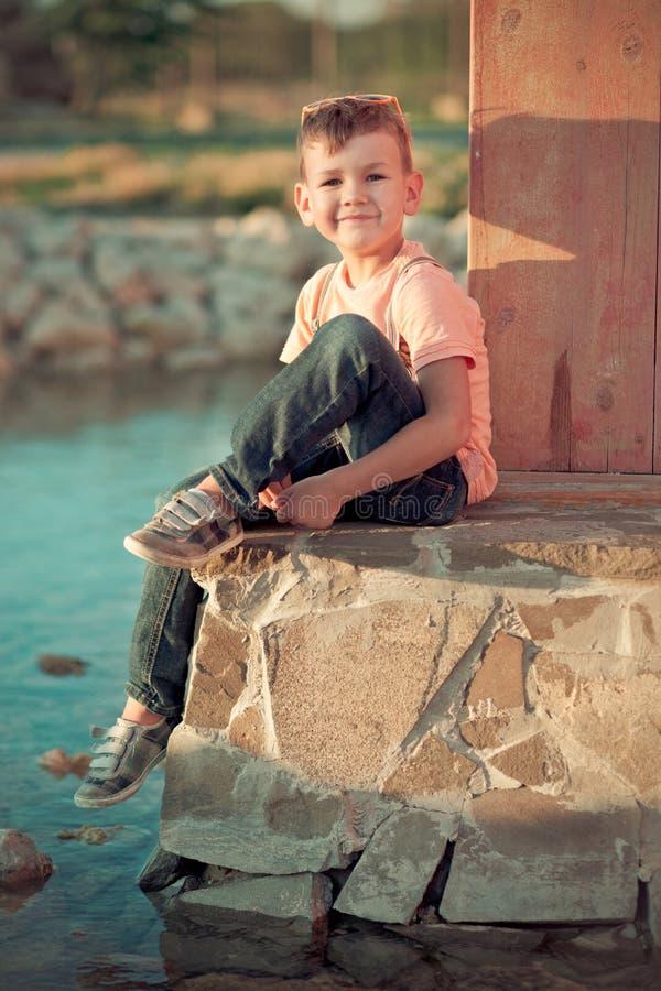Przystojny chłopiec dzieciak pozuje w lato centrali parku na zielonej świeżej trawie jest ubranym eleganckich odzieżowych i słońc fotografia royalty free
