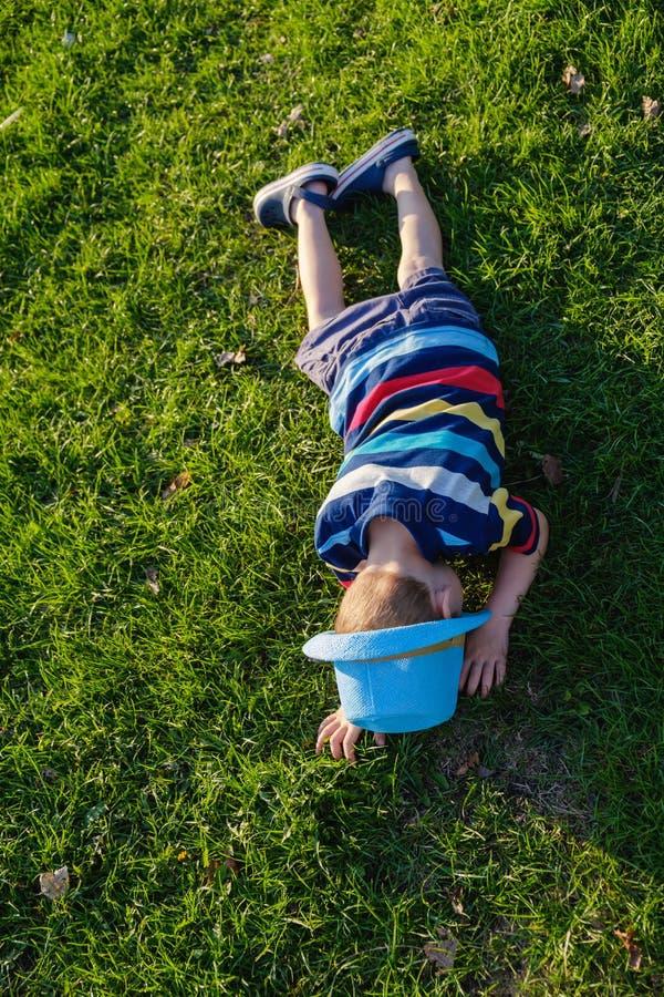 Przystojny chłopiec lying on the beach na trawie Mała marzycielka kłama w łące z kapeluszem Dziecko w naturze na zewnątrz miasta  obrazy royalty free