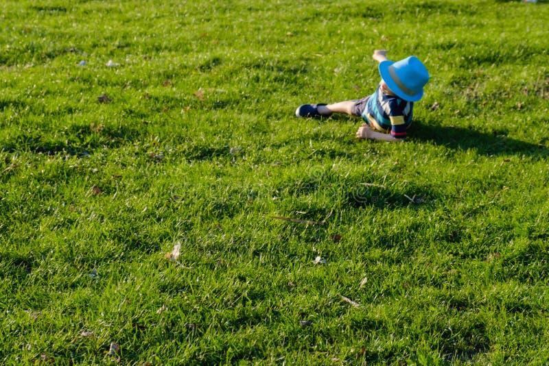 Przystojny ch?opiec lying on the beach na trawie Ma?a marzycielka k?ama w ??ce z kapeluszem Dziecko w naturze na zewn?trz miasta  zdjęcia stock