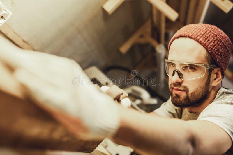 Przystojny cieśla prostuje kawałek drewno obrazy stock