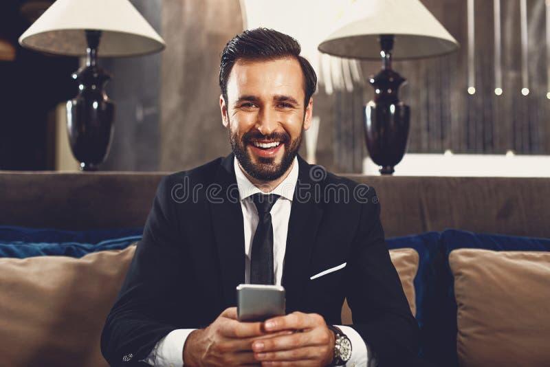 Przystojny, ciemnowłosy mężczyzna uśmiecha się i wygląda na szczęśliwego obraz stock