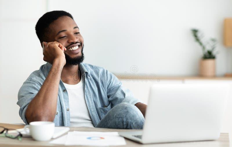 Przystojny czarny mężczyzna rozmawiający przez telefon w miejscu pracy zdjęcie royalty free