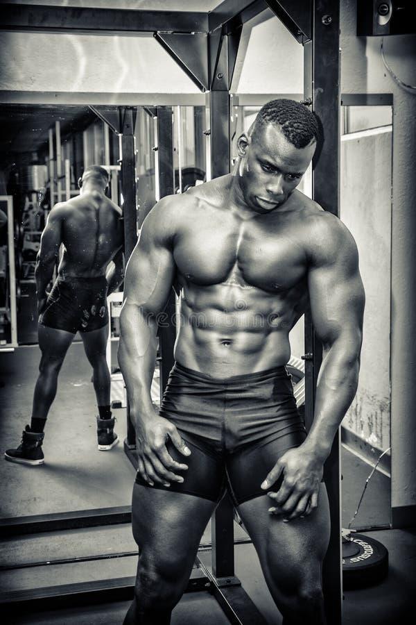 Przystojny czarny męski bodybuilder odpoczywa po treningu w gym zdjęcie stock