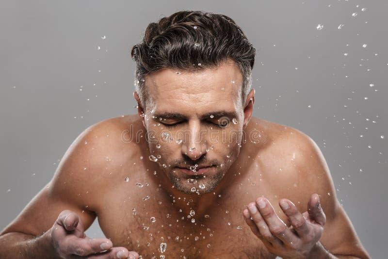 Przystojny dorośleć mężczyzna myje jego twarz fotografia stock