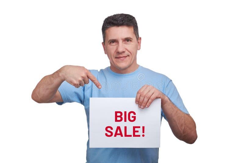 Przystojny dorosły mężczyzny mienia prześcieradła papier z tekst dużą sprzedażą robić wskazywać gest i obraz stock