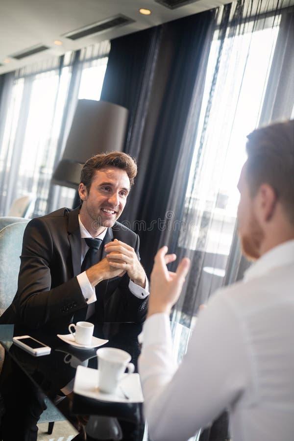 Przystojny dwa biznesmena spotkania w kawiarni zdjęcia stock