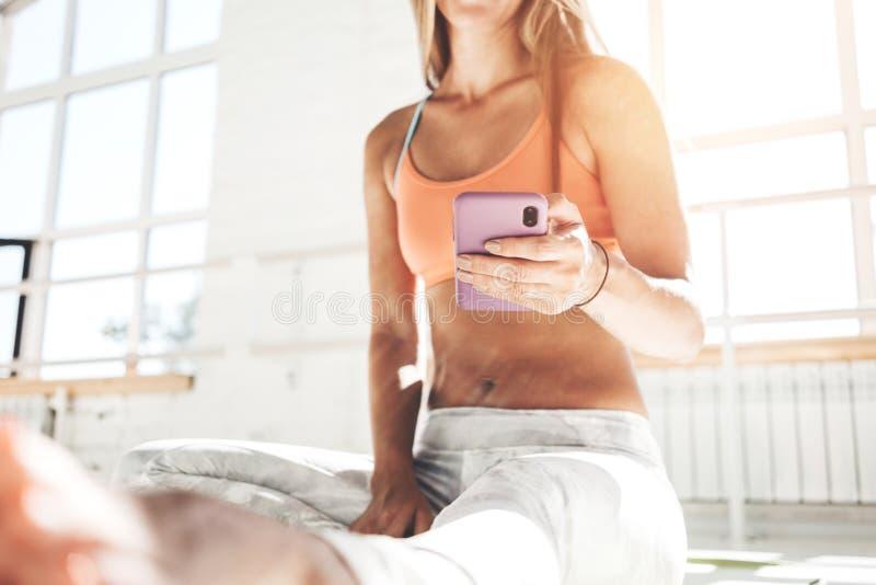 Przystojny dysponowany kobiety obsiadanie na joga macie i chwyta smartphone w ręce liczy kalorie w sprawności fizycznej zastosowa zdjęcie royalty free