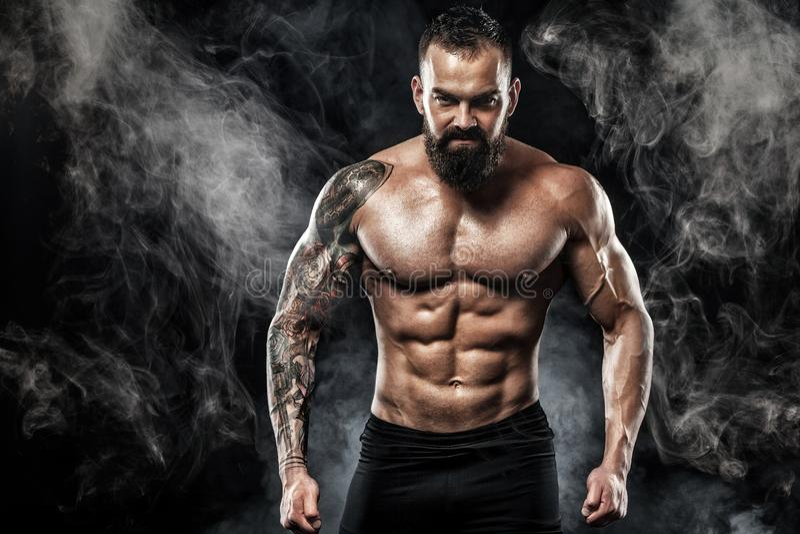 Przystojny dysponowany mężczyzna pozuje być ubranym w cajgach z tatuażem Bawi się pojęcie odizolowywającego na czarnym tle i faso fotografia royalty free