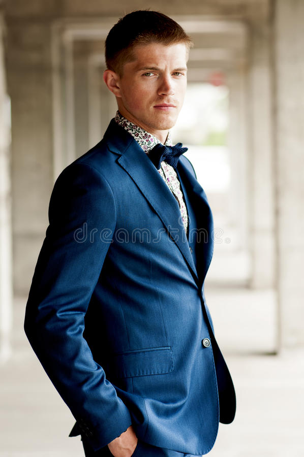 Przystojny elegancki mężczyzna jest ubranym błękitnego kostium z łęku krawatem fotografia stock