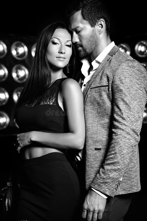 Przystojny elegancki mężczyzna w kostiumu z piękną seksowną kobietą pozuje na czarnym studiu zaświeca tło obraz royalty free