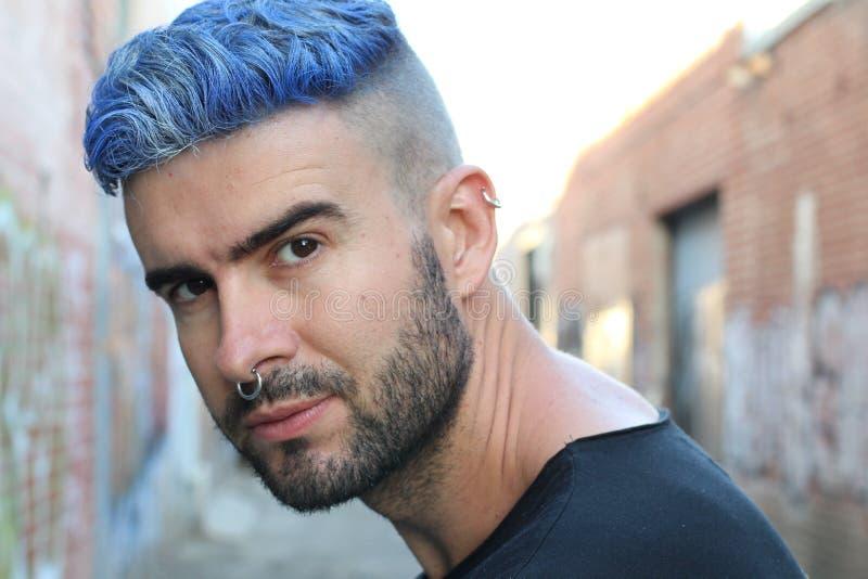Przystojny elegancki młody człowiek z sztucznie barwiony błękit farbującym włosy podcinał fryzurę, brodę i piercings z kopii prze zdjęcia royalty free