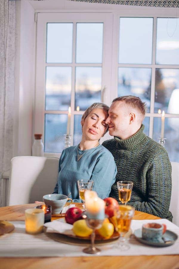 Przystojny facet całuje jego uroczej dziewczyny podczas gdy siedzący przy stołem obrazy stock