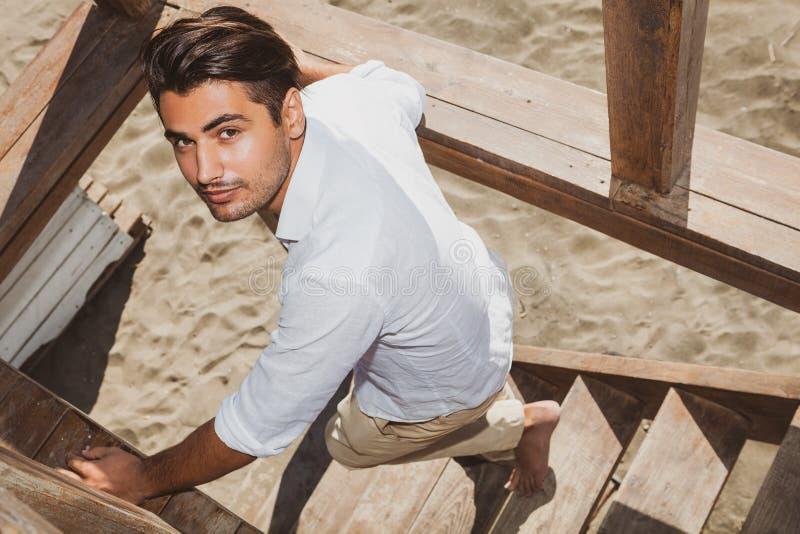 Przystojny facet iść z modnymi fryzura w dół drewnianymi schodkami podczas gdy patrzejący obrazy royalty free