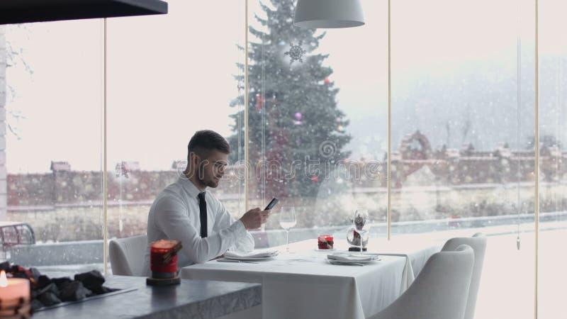 Przystojny facet patrzeje jego handwatches i czeka dziewczyny, młody człowiek pomaga jego dziewczyny pomieszczać na krześle obrazy royalty free