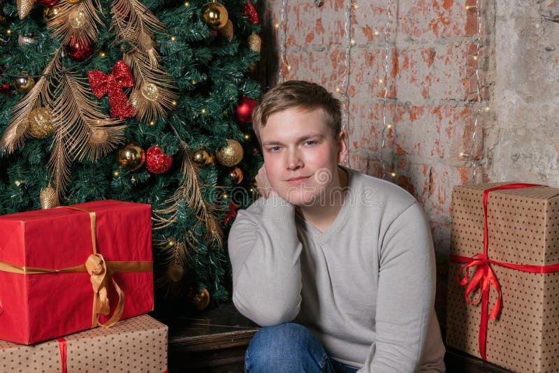 Przystojny facet siedzi pod drzewem otaczającym pudełkami prezenty Boże Narodzenia i prezenty zdjęcie stock