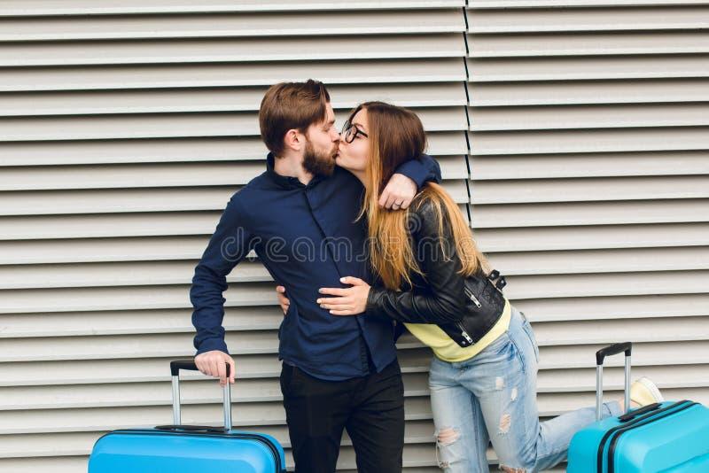 Przystojny facet z brodą w czarnej koszula całuje z dziewczyną z długie włosy na szarość paskującym tle między walizkami obraz stock