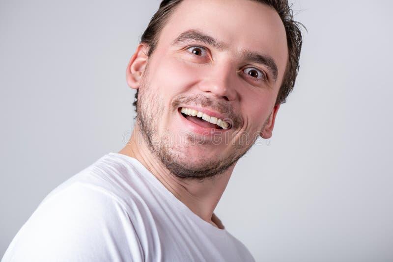 Przystojny facet z jeży się w białej koszulce robi śmiesznym grymasom na jego twarzy fotografia stock