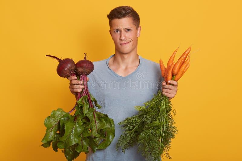 Przystojny fairhaired mężczyzna trzyma świeżych warzywa w rękach, młody surowy foodist decyduje co jeść buraki lub marchewki odiz obraz royalty free