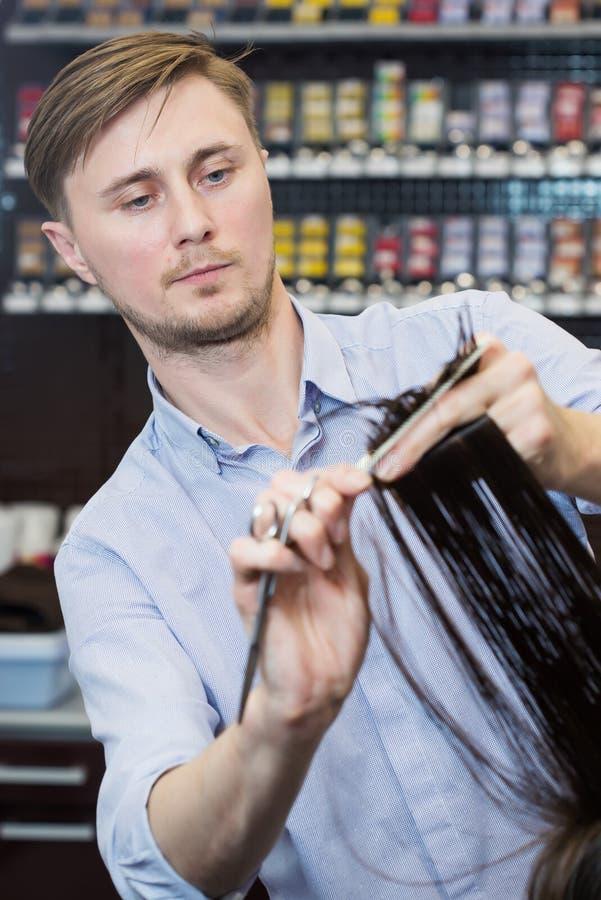 Przystojny fryzjer robi ostrzyżeniu zdjęcia stock