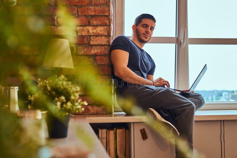 Przystojny grecki uczeń trzyma laptop podczas gdy siedzący na nadokiennym parapecie w studenckim dormitorium fotografia stock