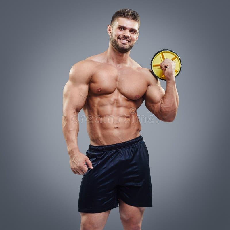 Przystojny gym trenera facet na popielatym tle zdjęcie stock