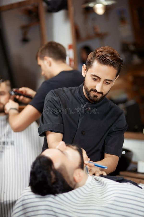 Przystojny hairstylist w fryzjera męskiego sklepu tnącym chlebie z żyletką dla brunet mężczyzna zdjęcia royalty free