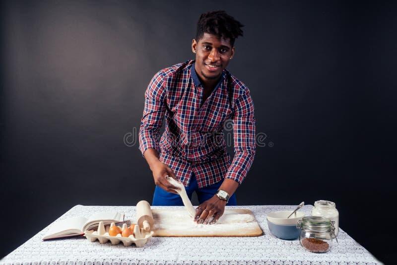 Przystojny i młody, afro-afrykański człowiek przygotowujący ciastka domowe... - American Pie ze świeżych rąk brudnych mąką, na obraz royalty free