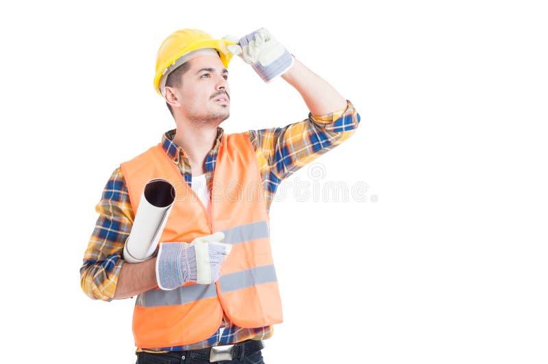 Przystojny inżynier trzyma staczającego się papierowego plan przyglądającego up i zdjęcia royalty free