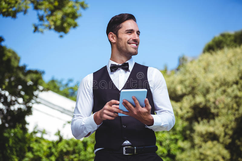 Przystojny kelner używa pastylka komputer obraz royalty free
