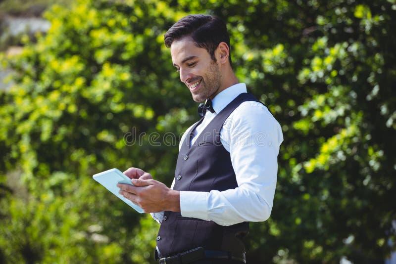 Przystojny kelner używa pastylka komputer zdjęcie stock