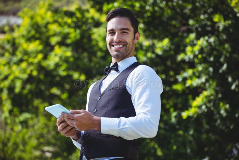 Przystojny kelner używa pastylka komputer zdjęcia royalty free