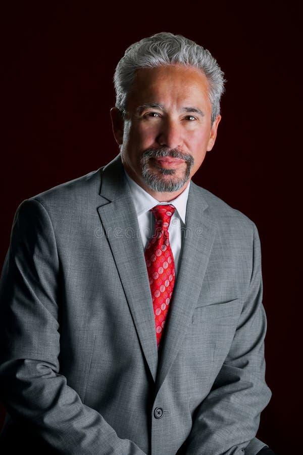 Przystojny Latynoski biznesmen Opiera w studia świetle zdjęcia stock