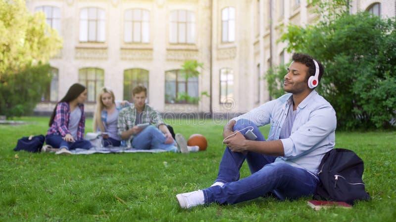 Przystojny Latynoski studencki obsiadanie na trawie i cieszyć się muzyka w hełmofonach obraz royalty free