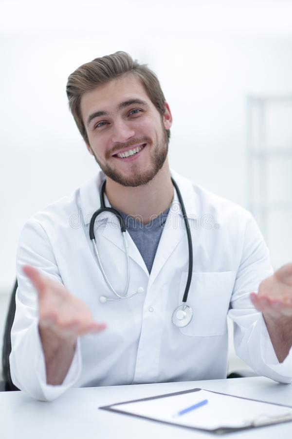 Przystojny lekarz medycyny w białym żakiecie oferuje jego rękę obrazy royalty free