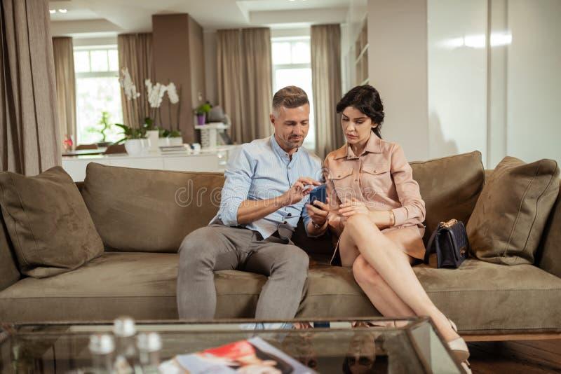 Przystojny mąż pokazuje fotografię na telefonie jego żona zdjęcie stock