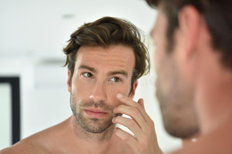 Przystojny mężczyzna bierze opiekę jego skóra zdjęcia royalty free