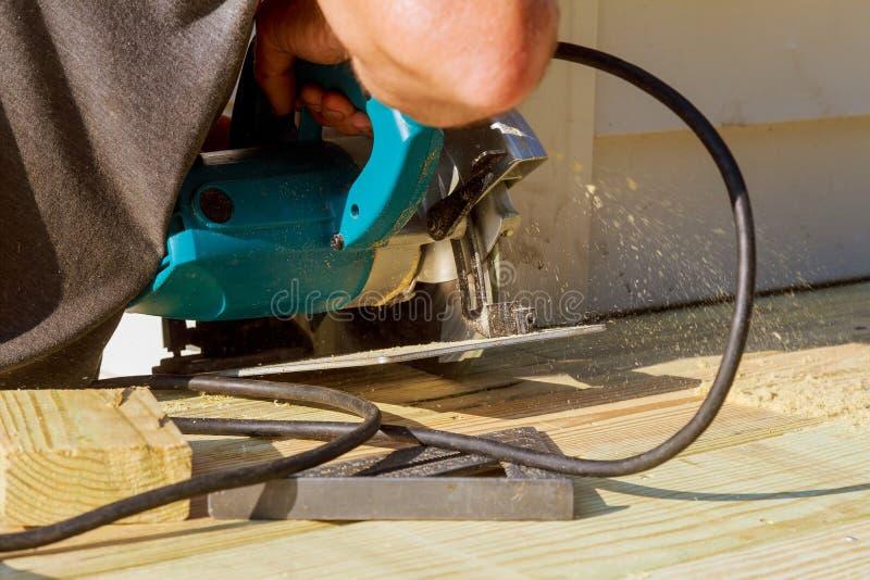 przystojny mężczyzna cieśla używa kurendę zobaczył instalować drewnianego podłogowego plenerowego taras w nowym domu zdjęcie stock