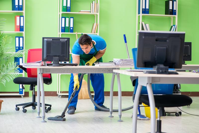 Przystojny mężczyzna cleaning biuro z próżniowym cleaner obrazy royalty free
