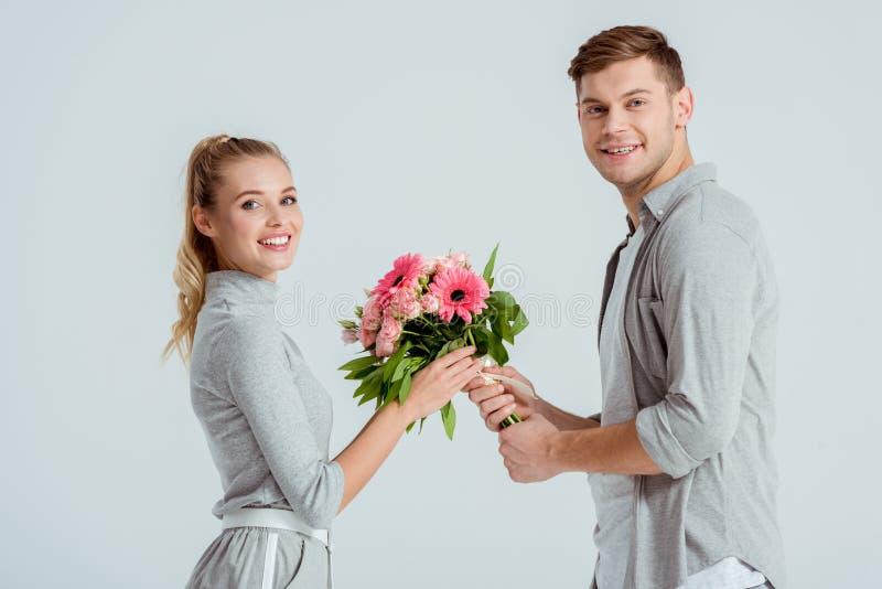 przystojny mężczyzna daje kwiatu bukietowi piękna uśmiechnięta kobieta odizolowywająca zdjęcia royalty free
