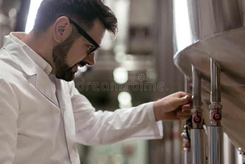 Przystojny mężczyzna działanie jako piwowar obraz stock