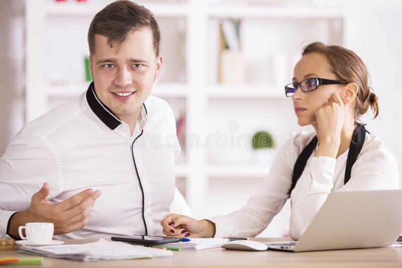 Przystojny mężczyzna i kobieta w biurze obrazy stock