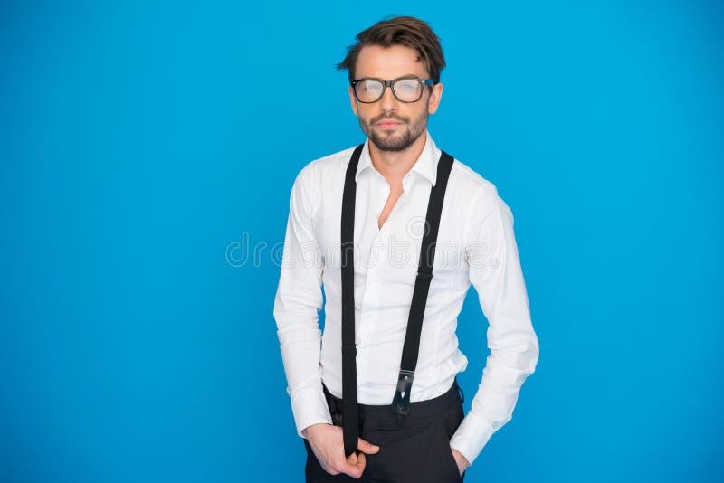 Przystojny mężczyzna jest ubranym białych brasy i koszula na błękicie zdjęcie stock